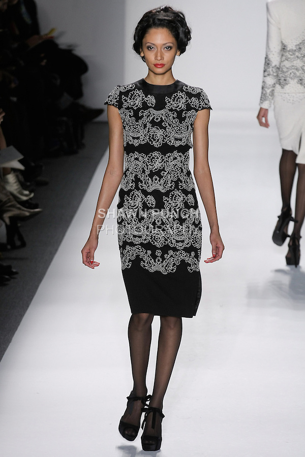 "Model walks runway in a black doublefaced wool crepe cocktail dress, overlayed w/black+ivory reembroidered french lace, from the Zang Toi Fall 2012 ""Glamour At Gstaad"" collection, during Mercedes-Benz Fashion Week New York Fall 2012 at Lincoln Center."