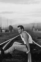 Man in a tank top sitting on railroad tracks in New Mexico