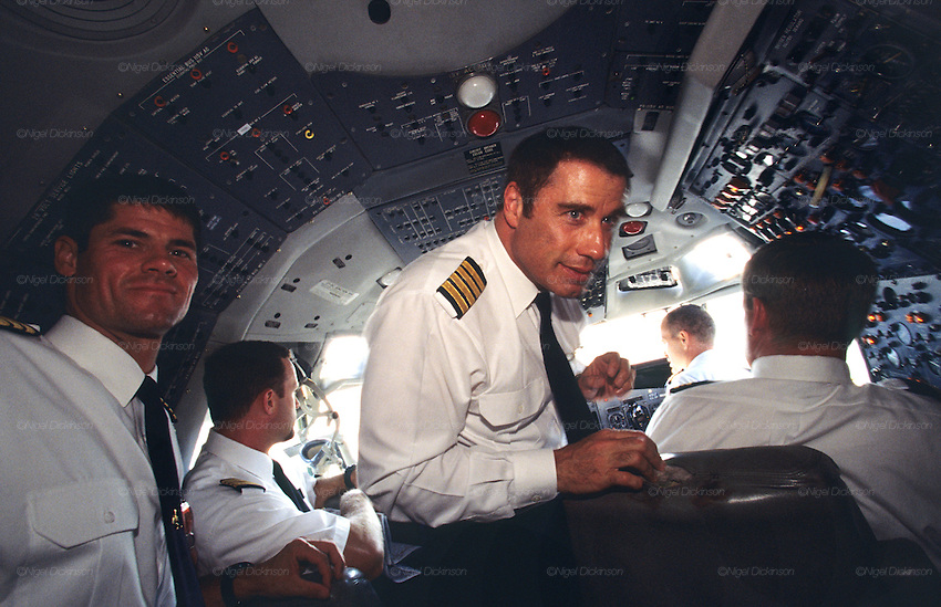 """John Travolta, captain and pilot, of his own jumbo jet, in the cockpit of his aircraft...John Travolta is pilot of his very own jumbo jet, a 1964 Boeing 707-100 series. In 2003, John Travolta flew his jumbo jet around the world, in partnership with Quantas, to rekindle confidence in commercial aviation, and to remind us that elegance and style are a part of flying. The crew are dressed in tailor made authentic uniforms from the Quantas museum. The men's uniforms are styled on British Naval uniforms and the ladies' designed by Chanel. His jumbo jet sports a personalised number plate N707JT which speaks for itself. The aircraft is named """"Jett Clipper Ella"""" dedicated to his son and daughter. This jumbo together with his other aircraft are housed in purpose built hangars at his home in Florida, USA."""