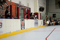 A view of one side of the Orange County Roller Girls' track as it is typically setup at The Rinks (a roller hockey facility).  From front to back we have Pack Man (a scorekeeper), Sir Racha (scoreboard operator), Invader Grim (a scorekeeper), two announcers, and Ivanna Cocktail (outside whiteboard) standing holding a whiteboard.