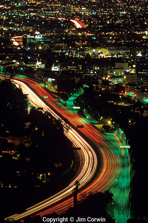 Sunrise over LA with car light streaks on Highway 101 from Mulholland Drive above LA, Los Angeles, California USA..