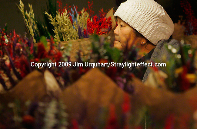 Jim Urquhart/Straylighteffect.com A woman sells flowers at the Pike Place Market in Seattle, Washington. 12/22/2009 - Jim Urquhart/Straylighteffect.com