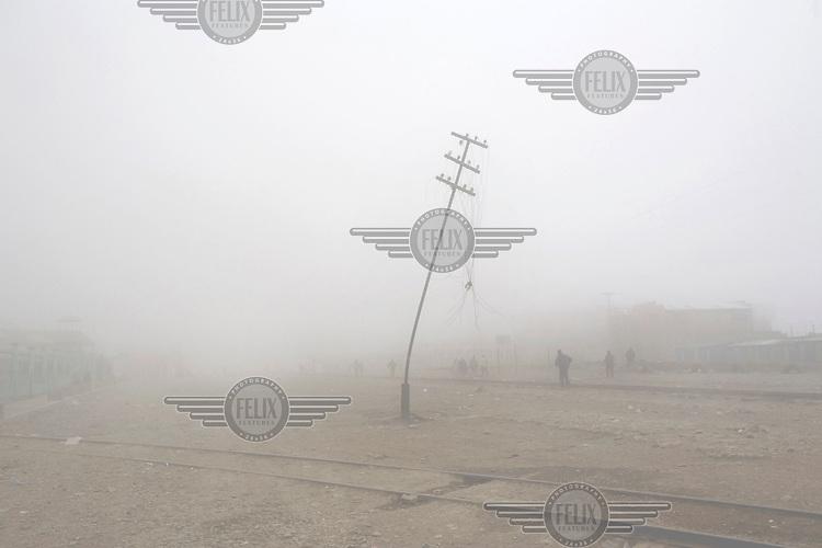 On a foggy street in El Alto people walk past a broken electricity pylon..