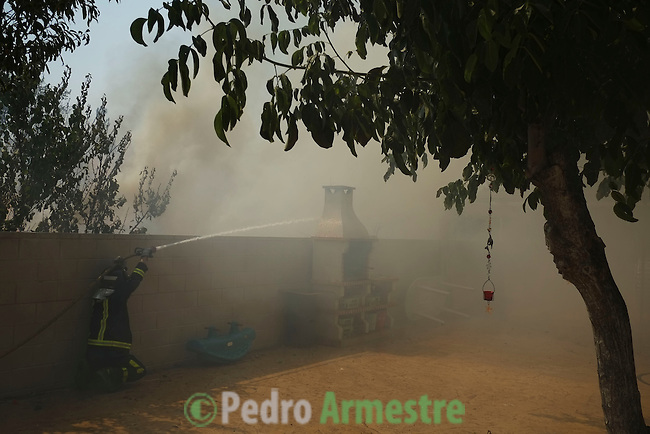 Smoke billows from properties at the site of a wildfire in tres cantos