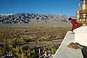 A monk looks out over the Indus River Valley from Thiksey Monastery in Ladakh, India.