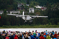 Airplane used for parachute jumping makes a low pass during opening ceremony. The Extremesport Week, Ekstremsportveko, is the worlds largest gathering of adrenalin junkies. In the small town of Voss enthusiasts in a varitety of extreme sports come togheter every summer to compete and play.© Fredrik Naumann