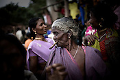 An elderly woman is seen smoking a country cigar while other Kondh tribes get together to celebrate their annual festival in Lanjigarh, Orissa, India.
