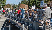 Marchers in the Saturday November 5 Occupy Orange County, Irvine walk across a bridge on Culver St.  The backs of many signs are visible.