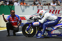 Jun. 2, 2012; Englishtown, NJ, USA: A crew member for NHRA pro stock motorcycle rider Hector Arana Jr lines him up in the groove during qualifying for the Supernationals at Raceway Park. Mandatory Credit: Mark J. Rebilas-