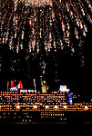 The Queen Mary 2 passes under the Statue of Liberty tonight while fireworks burst overhead celebrating the departure of the Queen Mary 2, the Queen Elizabeth and the Queen Victoria from New York City.