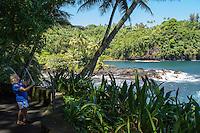 A tourist with a selfie stick takes photos along the coastline at Hawai'i Tropical Botanical Garden, Onomea, Big Island of Hawaiʻi.