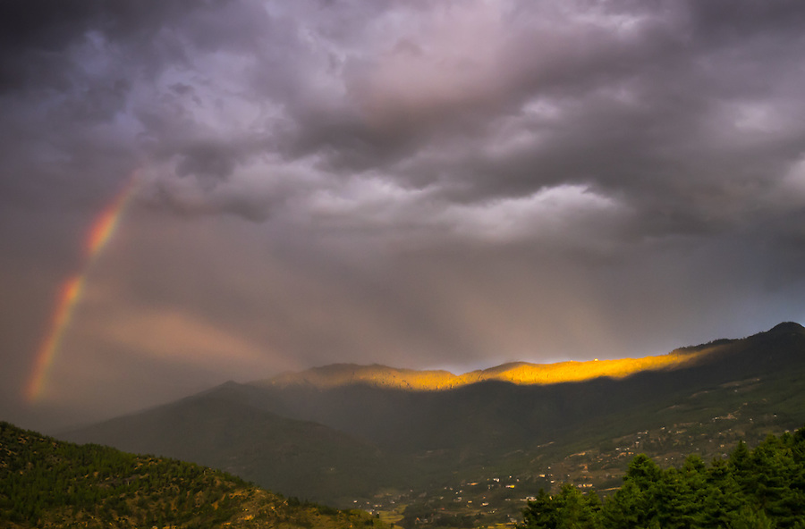 PARO, BHUTAN - CIRCA October 2014: Storm rolling into the mountains near Paro with rainbow