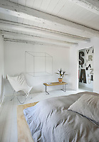 A simple white bedroom with a painted beamed ceiling and floorboards. A pot plant stands on a simple wooden table next to a canvas steel framed chair.