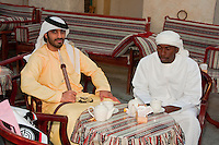 Doha, Qatar.  Two Emirati Arabs from Abu Dhabi, one of African Descent,  Relaxing in a Coffee Shop in the Doha Market.