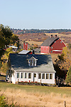 A farmhouse and several out buildings on a large farm in the foothills of the Rocky Mountains.
