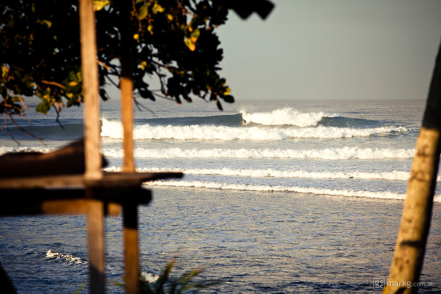 Classic Balian lineup breaking left and right over the rock reef.