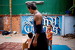 Unique Tuy, 5, KK's adopted son, watches his father after mediating a little squirmish with Srey Nich, 2, at Tiny Toones hip hop youth center, in Phnom Penh, Cambodia, on Thursday, April 22, 2010.