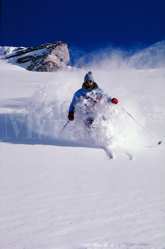 Incredibly light powder sprays up as a skier cuts through it on a cold, crisp day on an open slope. Ray Nelson. Utah, Alta Ski Resort.