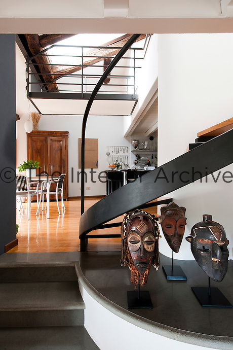 View of the open plan dining room and kitchen from the staircase with African masks on display