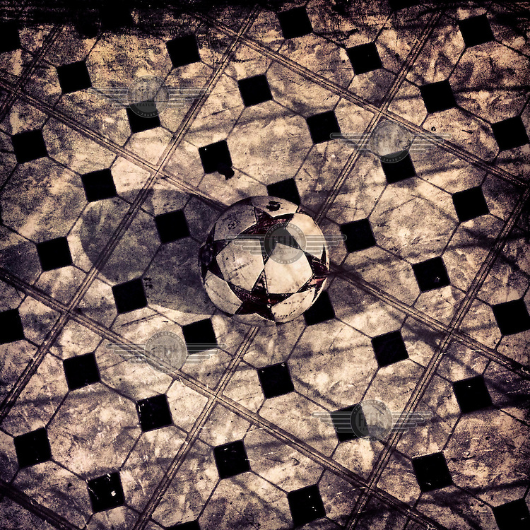 A soccer ball blends in with the floor tiles.