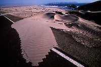 Strong coastal winds blow desert sand from a secluded beach attempting to reclaim the paved road. This point is desolate section of the Pan American highway south of Casma, Peru.