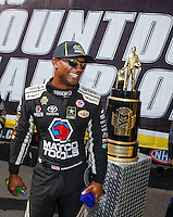 Sep 18, 2016; Concord, NC, USA; NHRA top fuel driver Antron Brown looks at the championship trophy prior to the Carolina Nationals at zMax Dragway. Mandatory Credit: Mark J. Rebilas-USA TODAY Sports