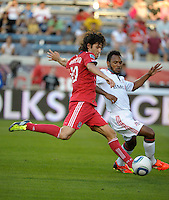 Chicago midfielder Sebastian Grazzini (10) takes a shot while being defended by Toronto midfielder Julian de Guzman (6)  The Chicago Fire defeated Toronto FC 2-0 at Toyota Park in Bridgeview, IL on August 21, 2011.