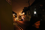 A woman walks down a dimly lit street on a rainy night in Dingle, Ireland.
