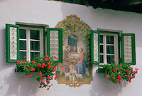 In the Austrian Tyrol a farmhouse mural depicting baby Jesus with a halo hugging lambs with his parents Mary and Joseph nearby.  This religious mural  painted in 1943  is sited between two flower troughs planted with geranium plants below windows with shutters.