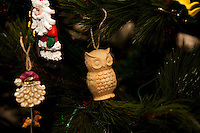 A wood-carved owl hangs on a Christmas tree.