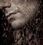 Closeup of a man unshaven chin with stubble and water running over it. Black and white sepia toned.