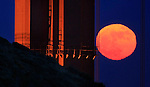 Golden Gate Bridge tower pairs up with the rising full moon seen in San Francisco, California.