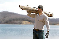 rugged man with a log over his shoulder standing by a lake in the Winter