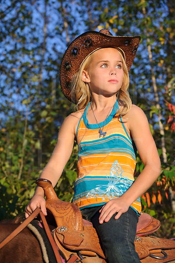 Young blonde cowgirl mounted on her horse in late evening golden light, wearing cowboy hat and looking into distance, Pennsylvania, PA, USA.
