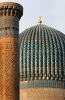Detail of minaret and cupola in the courtyard of the Gur-Emir Mausoleum, 1404, Samarkand, Uzbekistan. pictured at sunrise on July 15, 2010. Both are decorated with elaborately patterned tilework. Samarkand, a city on the Silk Road, founded as Afrosiab in the 7th century BC, is a meeting point for the world's cultures. Its most important development was in the Timurid period, 14th to 15th centuries.