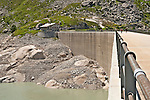 Wall of the Albigna dam hydroelectic station and Albigna Lake at 2,163 meters above Valley Bregaglia in Switzerland; kids practice rock climbing and ropes on the dam wall