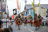 Parade, Somanomaoi Festival, Minami-soma City, Fukushima Prefecture, Japan, July 28, 2013. During the four-day-long Somanomaoi Festival members of old samurai families ride horseback through the town in traditional armour.  They also take conduct ceremonies at local shrines, take part in horse races, and compete on horseback to catch a flag launched into the air by fireworks.