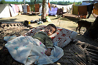 A toddler sleeps in a makeshift camp along a stretch of motorway in Swabi province. His family, refugees from Swat dsitrict, have made camp here because at present there's no space for them in the refugee camps. The Pakistani government began an offensive against the Taliban in the Swat Valley in April 2009, which led to a major humanitarian crisis. Up to two million civilians were estimated to have been displaced by the fighting.