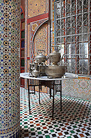 Ground floor central courtyard area with zellige tile decoration and a table set with silver tea ware, in a typical Tetouan riad, a traditional muslim house built around a courtyard, built in Moorish style with strong Andalusian influences, next to the Great Mosque or Jamaa el Kebir in the Medina or old town of Tetouan, on the slopes of Jbel Dersa in the Rif mountains of Northern Morocco. Tetouan was of particular importance in the Islamic period from the 8th century, when it served as the main point of contact between Morocco and Andalusia. After the Reconquest, the town was rebuilt by Andalusian refugees who had been expelled by the Spanish. The medina of Tetouan dates to the 16th century and was declared a UNESCO World Heritage Site in 1997. Picture by Manuel Cohen