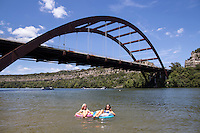 Two beautiful women relax and suntan while floating inner tubes on Lake Austin at the Loop 360 Bridge Park Beach, Austin, Texas.