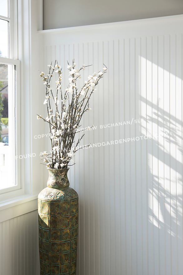 A tall vase of flowers sits by the window casting shadows across the white beaded board wall. This image is available through an alternate architectural stock image agency, Collinstock located here: http://www.collinstock.com