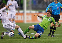 Seattle Sounders FC forward Brad Evans, right, and Vancouver Whitecaps FC  midfielder Jeb Brovsky slide for the ball during at Qwest Field in Seattle Saturday June 11, 2011. The game ended in a 2-2 draw.