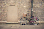 a maroon bicycle leaning against a brick wall in Cambridge, England