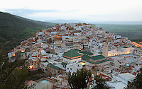 Evening view of the town of Moulay Idriss, over rooftops with the Mausoleum of Moulay Idriss I in the foreground, Meknes-Tafilalet, Northern Morocco. The town sits atop 2 hills on Mount Zerhoun and was founded by Moulay Idriss I, who arrived in 789 AD and ruled until 791, bringing Islam to Morocco and founding the Idrisid Dynasty. It is an important pilgrimage site for muslims. Picture by Manuel Cohen