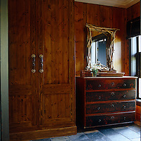 A mirror framed with twigs hangs over the rustic chest of drawers in the log cabin's bedroom