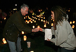 SOUTHBURY, CT 01/01/08-010108BZ01- Ken Aspis, of Southbury, hands a lit candle to Lisamarie Farina, 19, of Southbury, while setting up luminaries to form the word &quot;HOPE&quot; on the lawn outside Sacred Heart Church in Southbury Tuesday night.   The vigil was in remembrance of youth from the area who had untimely deaths recently.<br /> Jamison C. Bazinet Republican-American