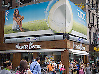 Advertising for Coca-Cola owned Zico coconut water beverage above a Caffe Bene coffee shop in the Chelsea neighborhood of New York on Tuesday, July 29, 2014. (© Richard B. Levine)