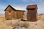 Rusting corrugated metal outhouse by weathered wooden cabin, Nevada