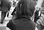 The aerial from a mobile telephone sticks through a womans hair whilst she has a conversation on her mobile telephone, Tokyo, Japan.