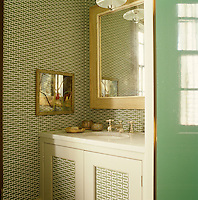 A marble-topped wash basin furnishes a corner of the bathroom which is lined with a patterned wallpaper